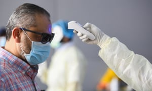 A health official checking the body temperature of a man in Kuwait City on 12 March 2020, the day after the WHO declared the coronavirus pandemic.