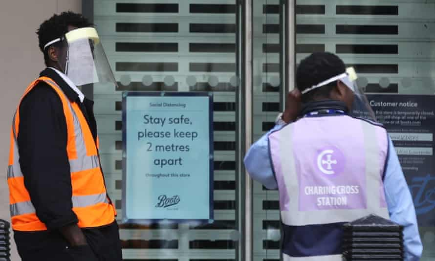 Members of railway staff wearing face shields stand in front of Charing Cross station in London