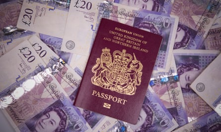 British passport on a pile of £20 notes