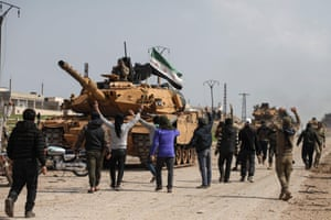 Syrians surround a Turkish tank as they attempt to block incoming joint Turkish and Russian military patrols on the M4 highway