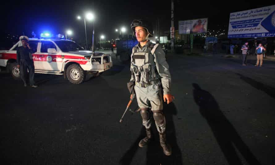 An Afghan policeman stands guard outside the Afghan police academy following the suicide bombing on Friday.