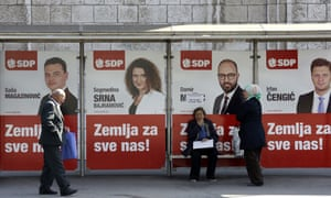 People pass by posters with candidates of the Social Democratic party (SDP) reading 'Country for all of us', in Sarajevo.