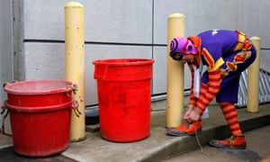 A clown ties his shoelace at the kerbside