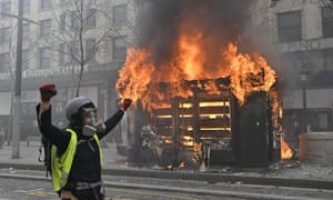 A protestor celebrates in front of a burning kiosk in the Champs-Élysées, Paris.