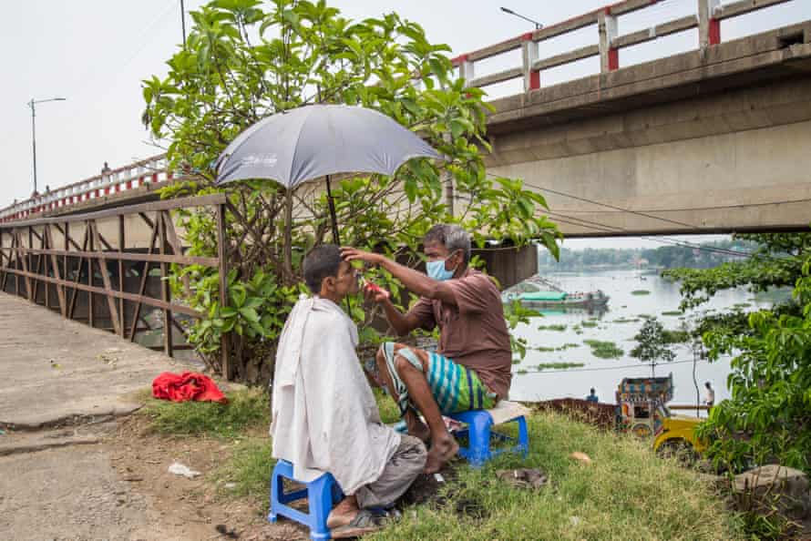A barber at the roadside shaves a worker beneath a parasol