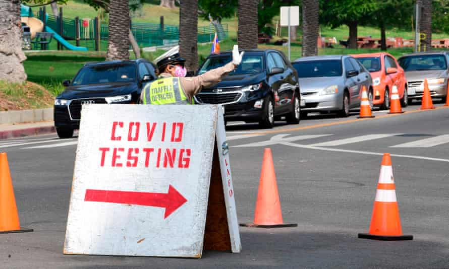 A traffic warden directs traffic as motorists arrive for Covid-19 tests at Dodger Stadium in Los Angeles, California on 8 October.