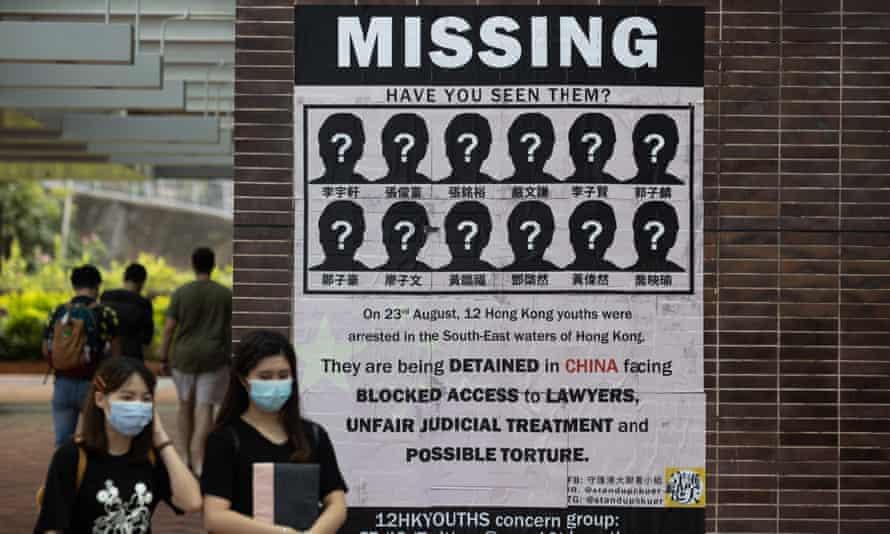 Students at the University of Hong Kong walk past a poster supporting 12 Hongkongers detained in China.