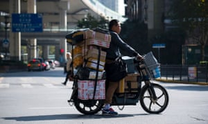 A delivery man on an electric bike crosses a street as he delivers parcels in Shanghai.
