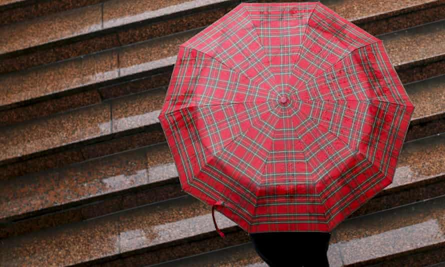 Woman leaves an underpass while holding an umbrella to protect herself from the rain