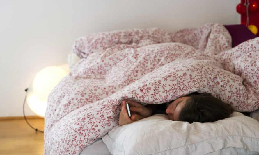 women under duvet covers reading smartphone