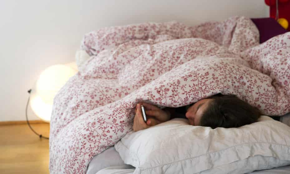 woman checks her phone while lying in bed