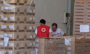 Red Cross volunteers store food at the logistical centre in Valencia in Spain