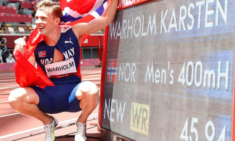 Karsten Warholm of Norway poses with the board showing his world record time in the men's 400m hurdles.