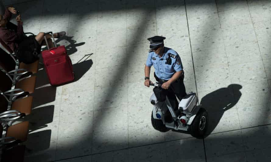 A mainland Chinese police officer patrols inside the departure hall of West Kowloon station in Hong Kong.