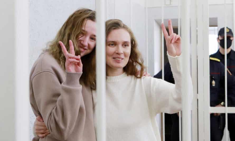 Katsiaryna Andreyeva, and Darya Chultsova make 'V' signs from cage in court