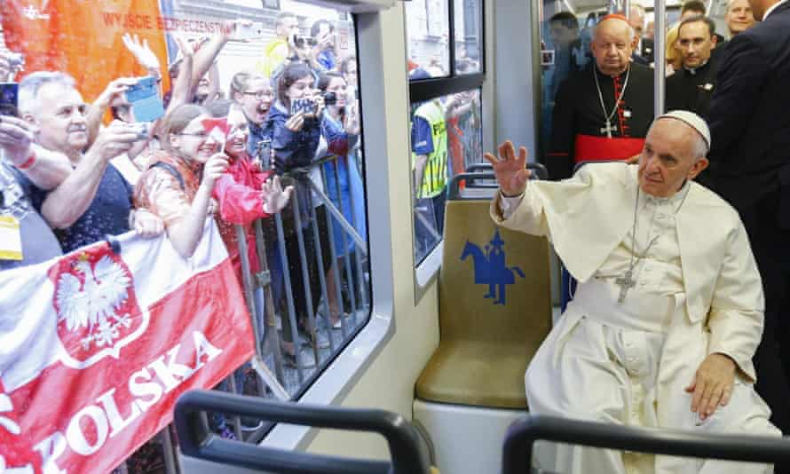 Pope Francis waves at crowds from the 'Tram del Papa'.