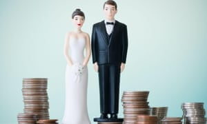 Figurines on a wedding cake surrounded by piles of coins
