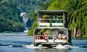 Murchison Falls are seen in the background as tourists enjoy a cruise along the Victoria Nile river in Uganda