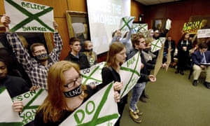Supporters of victims of sexual abuse by Larry Nassar hold up signs during a Michigan State Board of Trustees meeting on Friday.