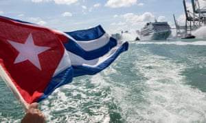 A man waves a Cuban flag as cruise ship Adonia sails out of Miami's port escorted by tugboats.