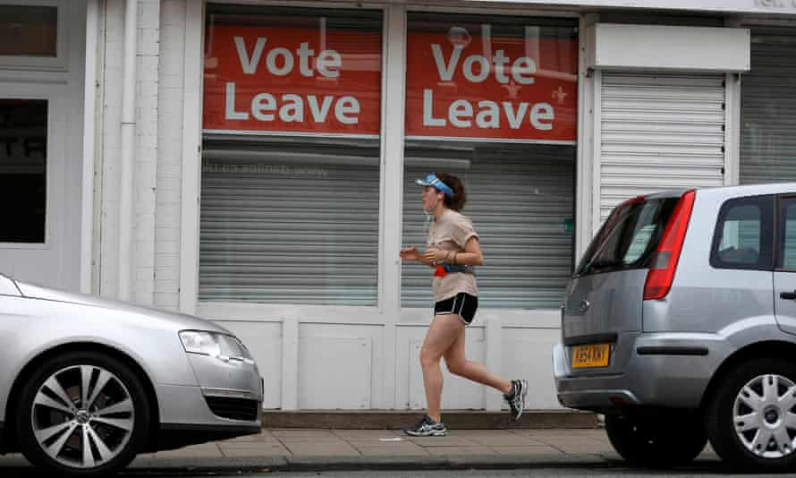 A woman runs past Vote Leave signs in the window of a shop