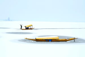A boatman steers his boat at the partially frozen Dal Lake after a snowfall