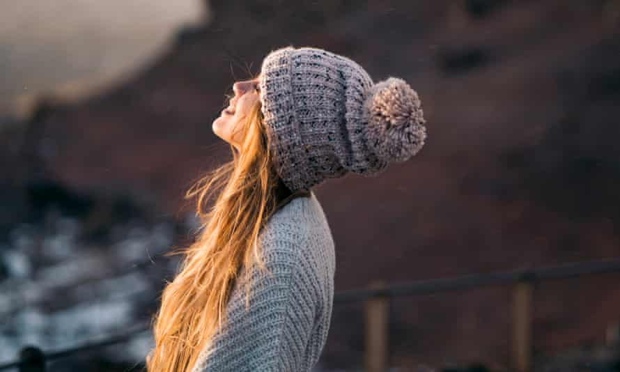 Side view of smiling woman in sunlight in warm clothing