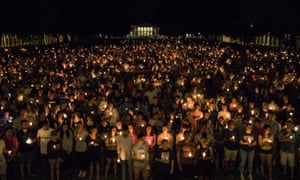 Thousands gather with candles to march along the path that white supremacists took the prior Friday on the University of Virginia Campus in Charlottesville, 16 August 2017.