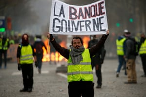A protester holds a poster with the words 'La banque gouverne' (the bank governs) during the demonstration in Paris
