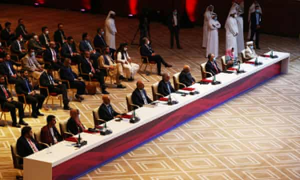 Delegates are seated before the talks at a hotel in Doha