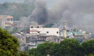 Smoke rises near a public market in Marawi.