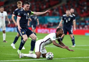 England's Raheem Sterling (right) reacts after a tackle by Scotland's Andrew Robertson.