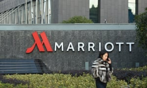 Woman on a mobile phone walks past a Marriott hotel