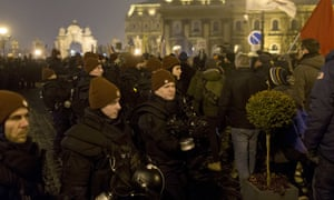 Protesters walk past riot police officers during an anti-government march in Budapest, Hungary.