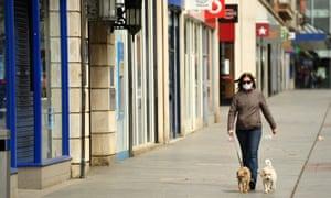 a woman walks her dog down an empty high street