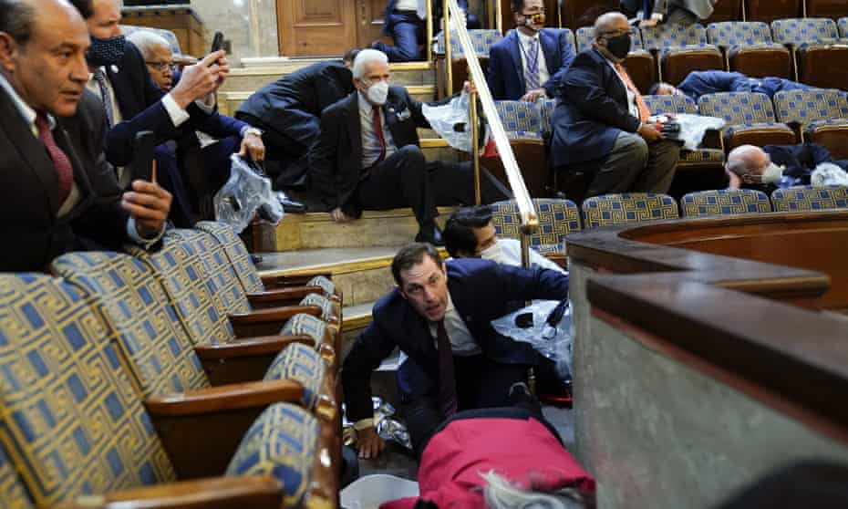 People shelter in the House gallery as protesters try to break into the chamber on 6 January.