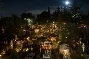 Mexico: Candles illuminate children's tombs in the San Gregorio cemetery on the outskirts of Mexico City. Families decorate the graves of departed relatives with marigolds and candles, and spend the night in the cemetery, eating and drinking as they keep company with their deceased loved ones