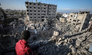 A Palestinian boy inspects the rubble of the Al-Aqsa TV's building after it was targeted by Israeli airstrikes in Gaza