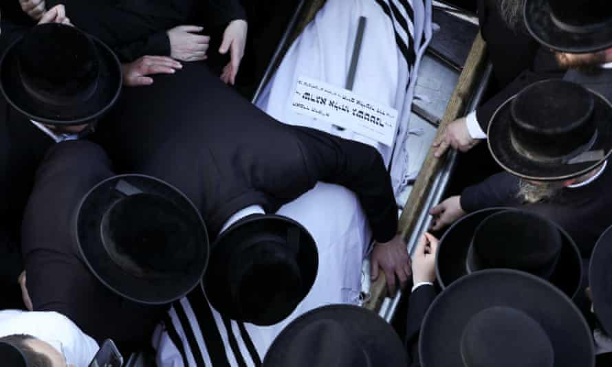 Ultra-Orthodox Jewish men mourn over the body of Shraga Eliyahu Gashtner, who died during Lag B'Omer, at his funeral in Jerusalem on 30 April.
