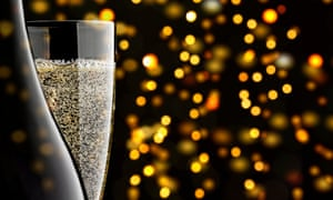 Champagne Glass and Champagne Bottle with sparkling yellow and orange lights in the background.