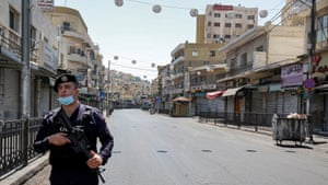 A policeman stands on guard while enforcing a curfew due to the Covid-19 coronavirus pandemic along a street in Jordan's capital Amman on 28 August, 2020.