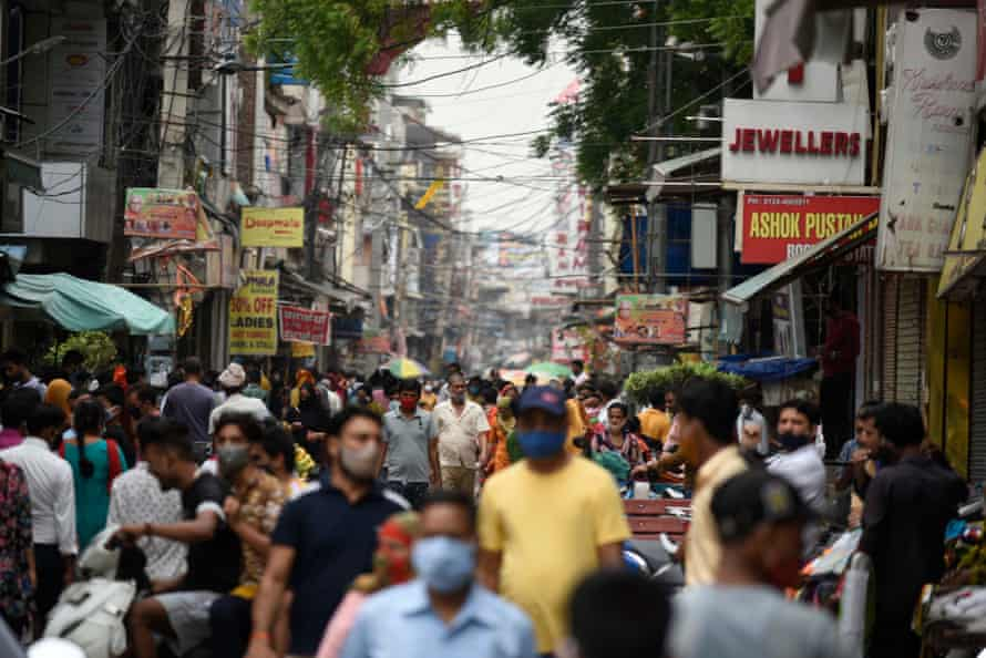 People flout social distancing norms as they throng a market for shopping, near Post Office, on June 13, 2021 in Gurugram, India.