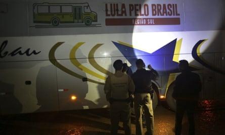 Police investigate a bus used by the campaign caravan carrying Brazil's former President Luiz Inacio Lula da Silva Tuesday.