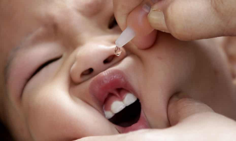 Health worker administers a vaccine to a baby at a local health center at the financial district of Makati, east of Manila