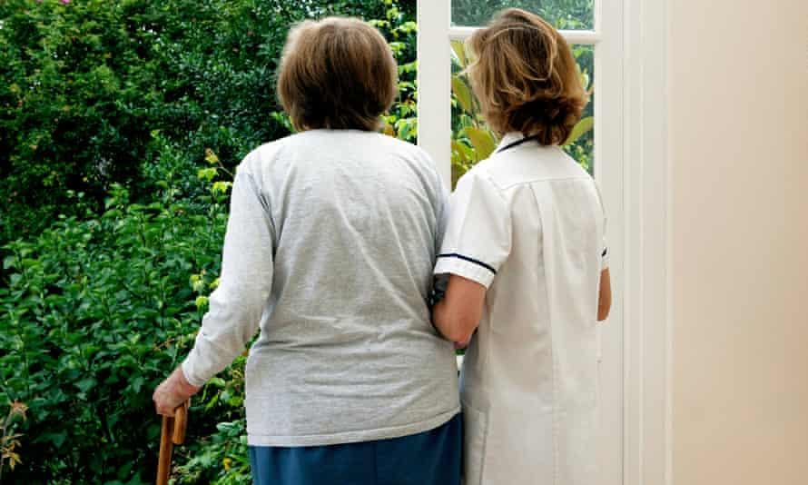 Nurse supporting elderly woman. Chiswick, London, UK