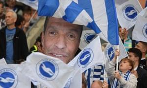 A Chris Hughton cutout is held aloft by Brighton fans