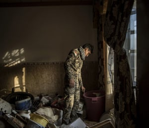 Kurdish Peshmerga forces inspect belongings left in a home