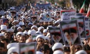 Clerics hold up pro-regime placards in Qom.