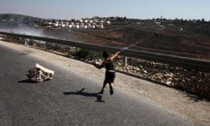 A Palestinian boy hurls a stone during a protest against the confiscation of Palestinian land to expand Jewish settlements in Nabi Saleh near Ramallah.