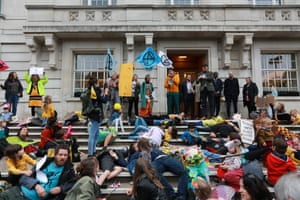 Alex Armitage of Extinction Rebellion Hackney Families speaks to the councillor Jon Burke on the steps of the town hall.